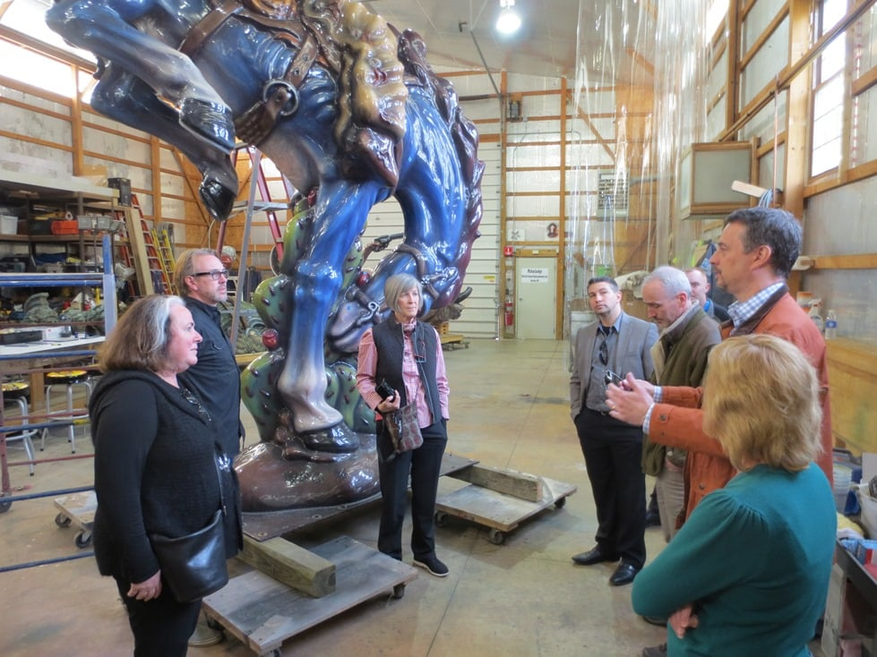 Members of the PPG corporation Jimenez sculpture conservation support team address Susan Jimenez (left), the executive director of the Luis A. Jimenez, Jr. Estate, conservator Jim Gwinner (center) and Smithsonian conservator Helen Ingalls (right). VAQUERO from the Smithsonian American Art Museum is behind them.