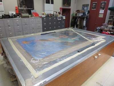 the painting DAWN is lined onto linen using the lab's large lining table